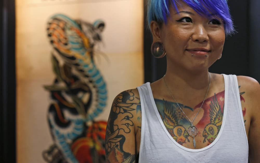 A woman with tattooed body stands at a design booth during the first International Hong Kong China Tattoo Convention in Hong Kong.