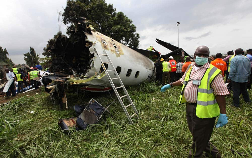 Rescue workers inspect the wreckage of a charter passenger jet which crashed soon after take off from Lagos airport, Nigeria.