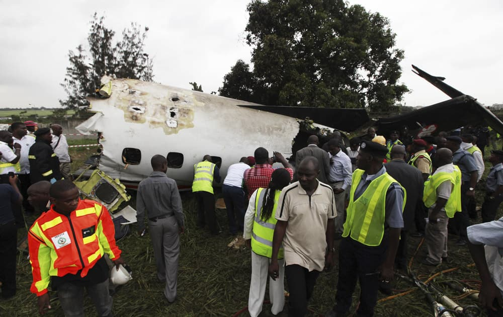 Rescue workers gather around the wreckage of a charter passenger jet which crashed soon after take off from Lagos airport, Nigeria.