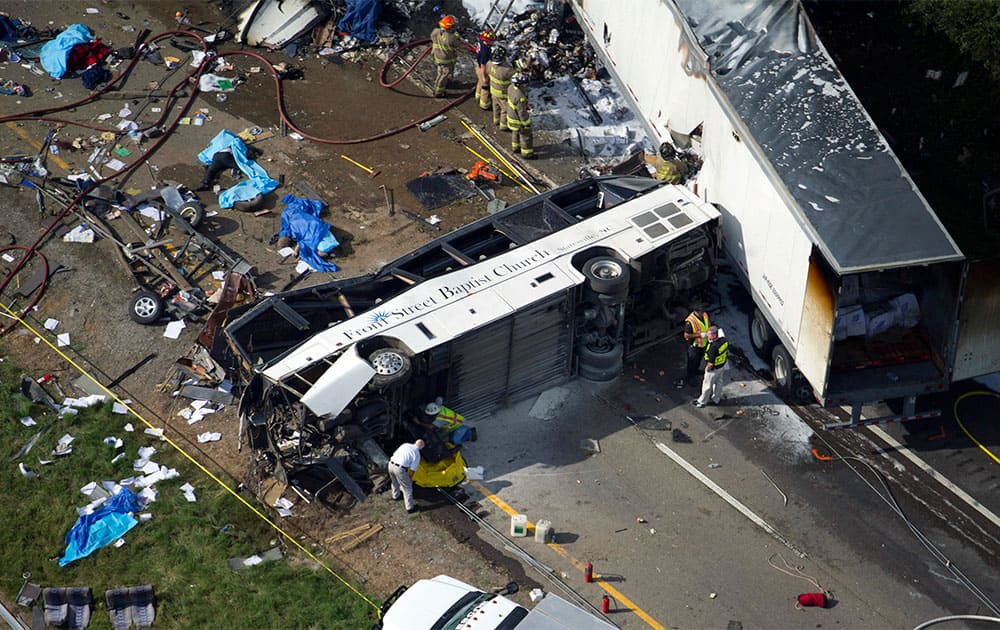 In this aerial photo, emergency workers respond to a crash involving a passenger bus, a tractor-trailer and an SUV near Dandridge, Tenn. Authorities said the bus, carrying members of a North Carolina church group, veered across the highway median and crashed into the other vehicles in a fiery wreck that killed several people.