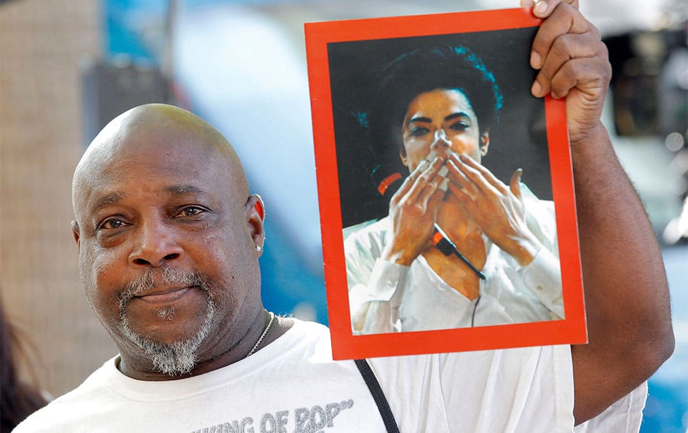 Vincent Woods, a Michael Jackson fan hold up a portrait of Jackson after the AEG Jackson trial verdict  in Los Angeles.