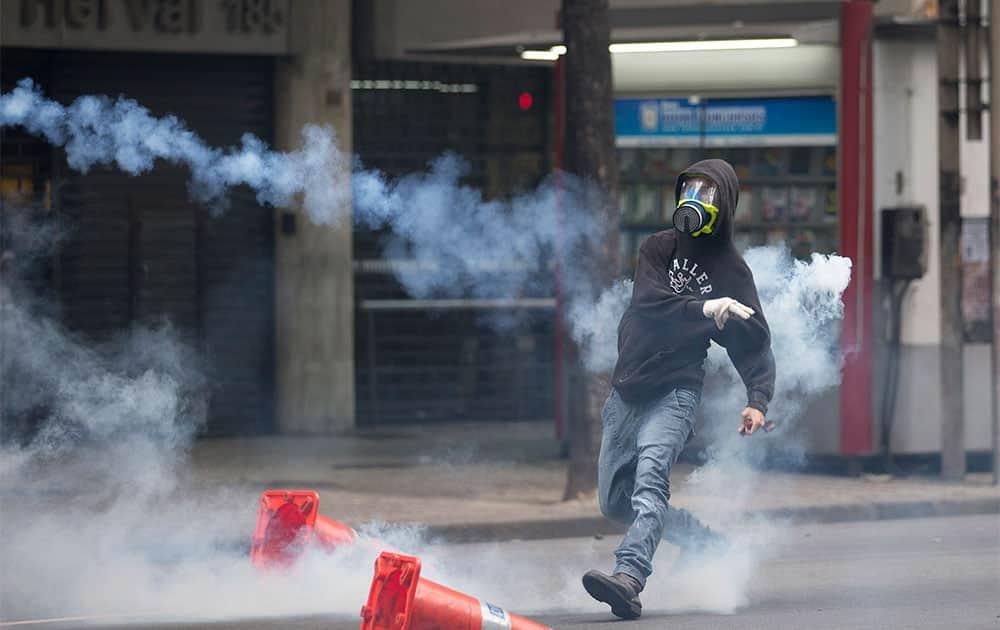 A protestor throws a tear gas toward police officers during a protest outside the City Council in Rio de Janeiro, Brazil.