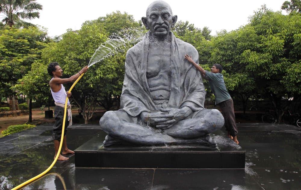People clean a statue of Mahatma Gandhi ahead of Gandhi Jayanti in Bhubaneswar.