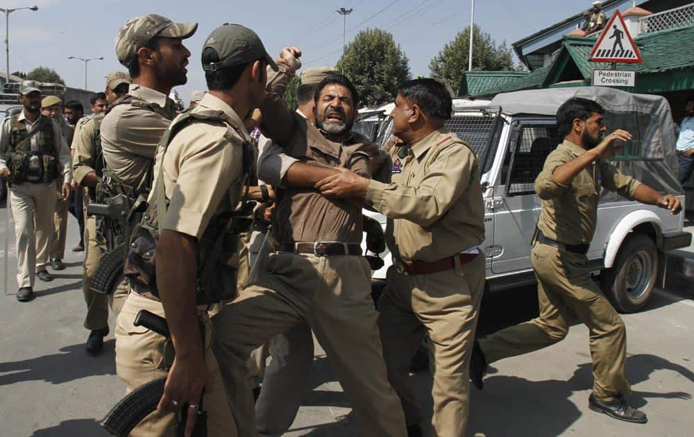 Policemen detain a Jammu and Kashmir government employee during a protest in Srinagar.