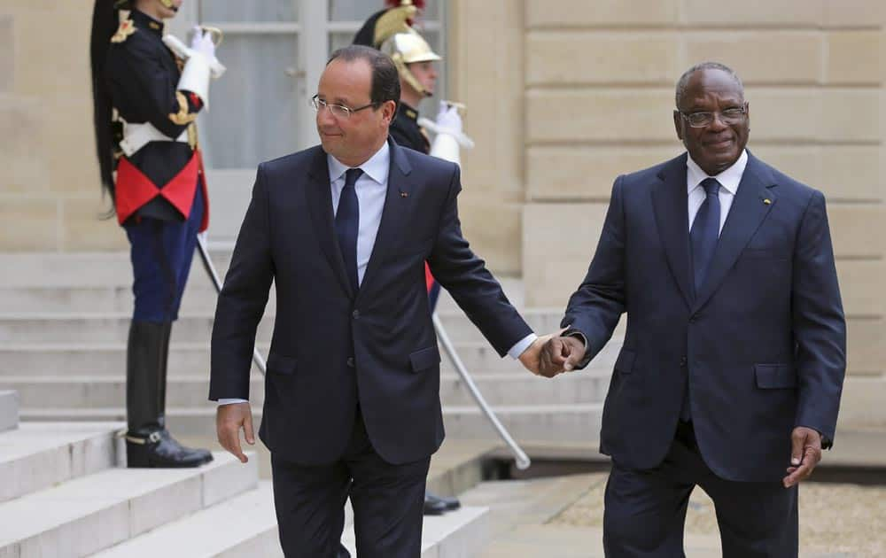 French President Francois Hollande, holds the hand of Mali President Ibrahim Boubakar Keita prior to their meeting at the Elysee Palace in Paris.