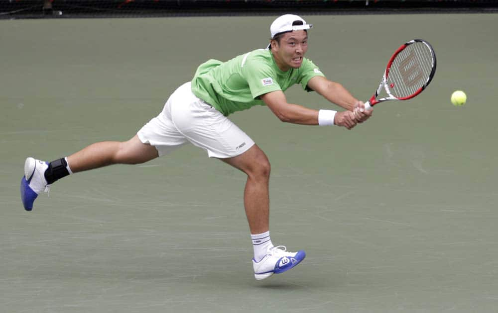 Tatsuma Ito of Japan returns the ball against Feliciano Lopez of Spain during their first round match at the Japan Open Tennis Championships in Tokyo.