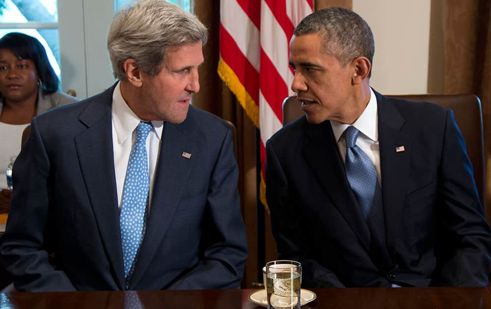 President Barack Obama talks with Secretary of State John Kerry before a cabinet meeeting in the Cabinet Room of the White House.