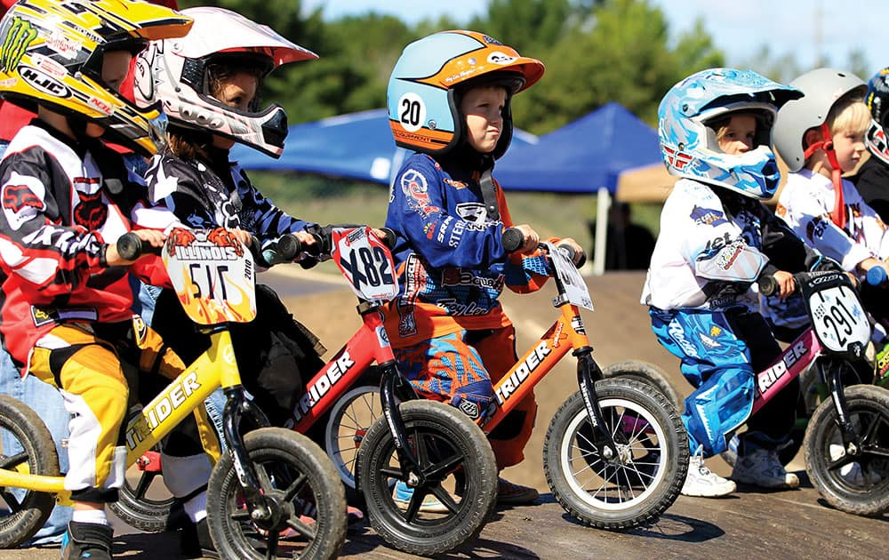 Three year old children line up for the STRIDER race at the 2012 USA BMX Badger State Nationals held in Wisconsin Rapids, Wis. Gathered at the starting line, they look like mini versions of BMX racers, decked out in helmets, jerseys and protective gear with number plates on their tiny bikes.