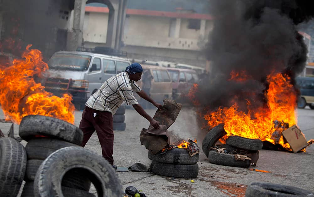 A demonstrator adds cardboard to burning tires blocking the capital`s main street during a protest against the government of President Michel Martelly in Port-au-Prince, Haiti.