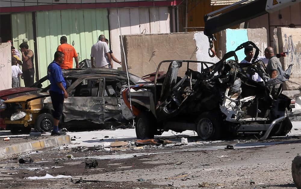 Citizens inspect the site of a car bomb attack in Baghdad, Iraq.