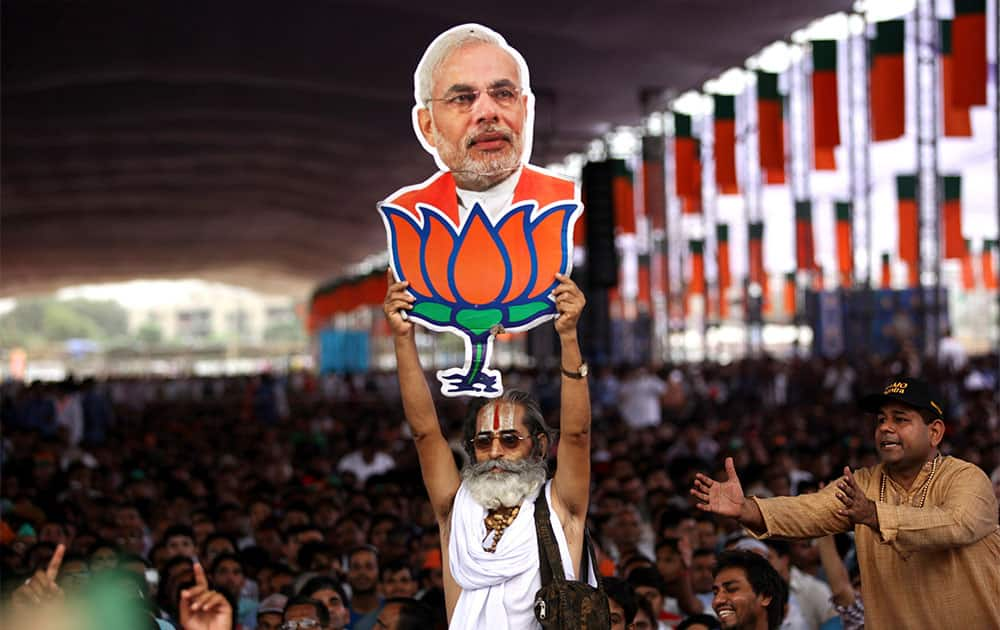 A supporter holds a cut-out photograph of India's opposition Bharatiya Janata Party (BJP) leader Narendra Modi with the party symbol lotus as he addresses a public rally in New Delhi.