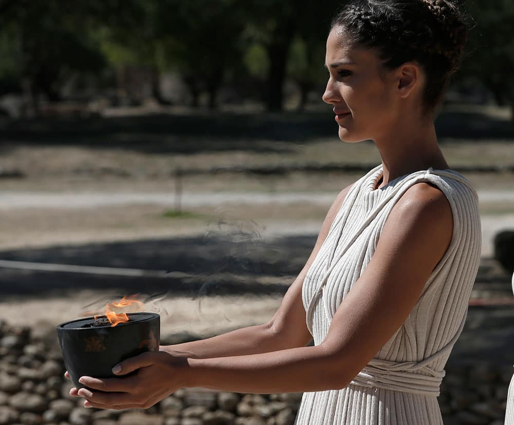 An actress in the role of a priestess carries the flame from the temple of Hera to the ancient Olympic Stadium, during the lighting of the Olympic flame at Ancient Olympia, in west southern Greece.