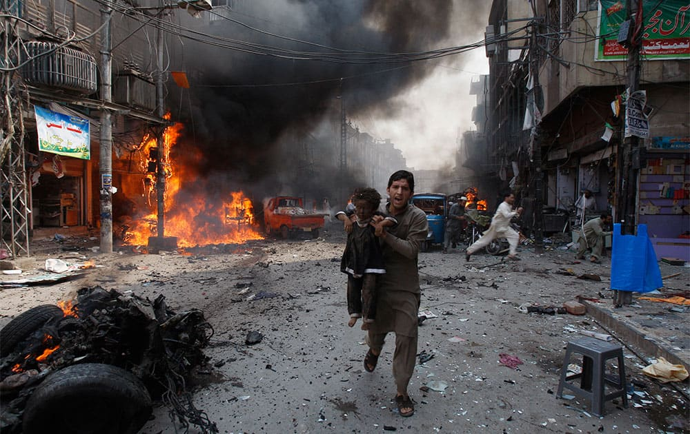A man carrying a child rushes away from the site of a blast shortly after a car exploded in Peshawar, Pakistan. A car bomb exploded on a crowded street in northwestern Pakistan, killing scores of people in the third blast to hit the troubled city of Peshawar in a week, officials said.