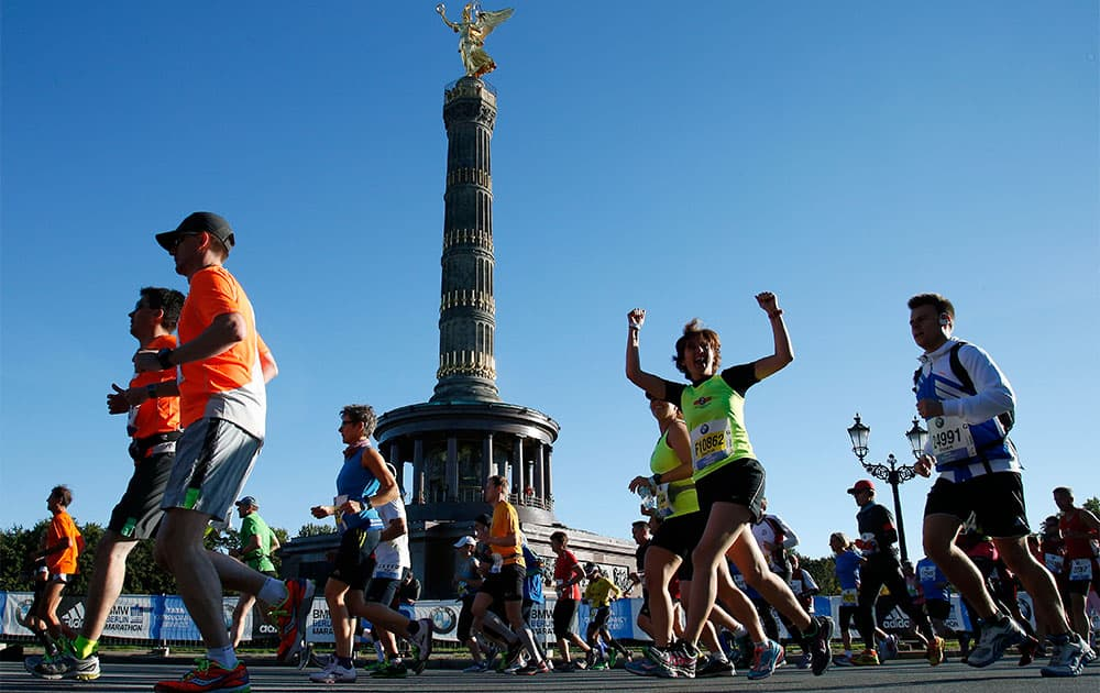 A runner raises her arms in front of the victory column just after the start of the 40th Berlin Marathon in front of the Brandenburg Gate in Berlin, Germany.  Some 40,000 runners take part in the event.
