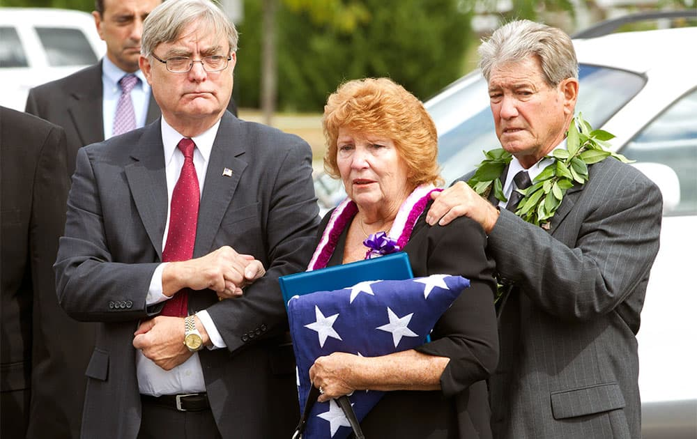 Shirley Ridgell and her husband Dick Ridgell, right, are comforted by their friend Michael W. Beasley, left, after the funeral service of their son Richard Michael Ridgell, 52, of Westminster, Md. at The Church at Severn Run, in Severn, Md.