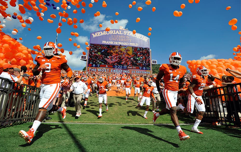 Clemson defensive tackle Tavaris Barnes (9), defensive back Martin Jenkins (14) and cornerback Garry Peters (26) run to the field before an NCAA college football game against Wake Forest,  in Clemson, S.C.