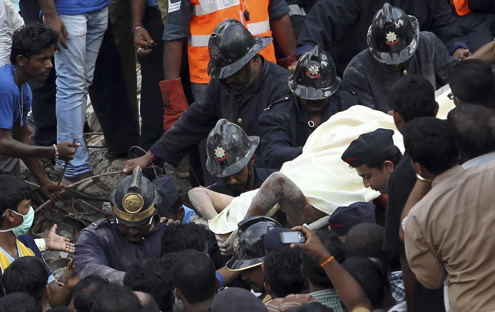 Rescue workers carry a survivor out of the debris of a building that collapsed, in Mumbai.