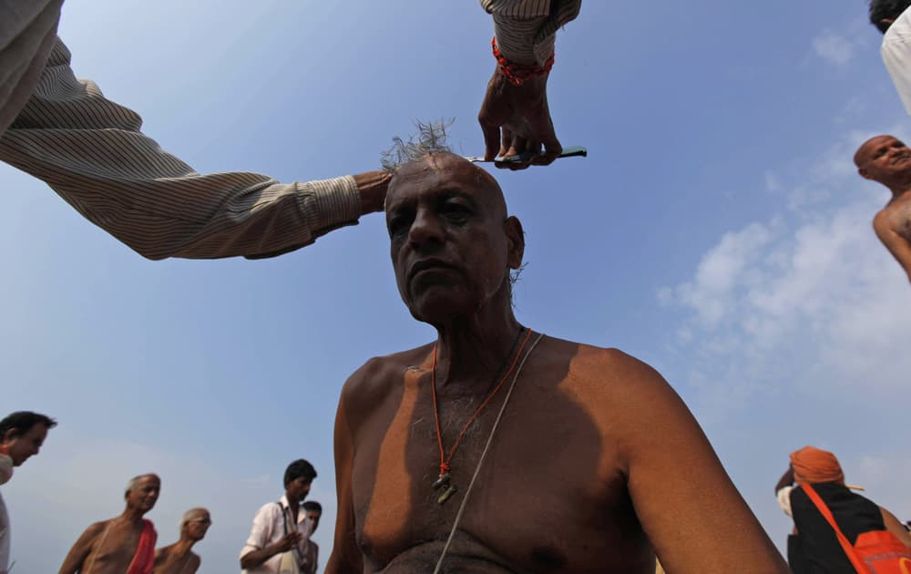 """A Hindu devotee gets his head shaved to perform """"Pind Daan"""" rituals, believed to bring peace of the souls of ancestors, on the banks of the River Ganges in Allahabad."""
