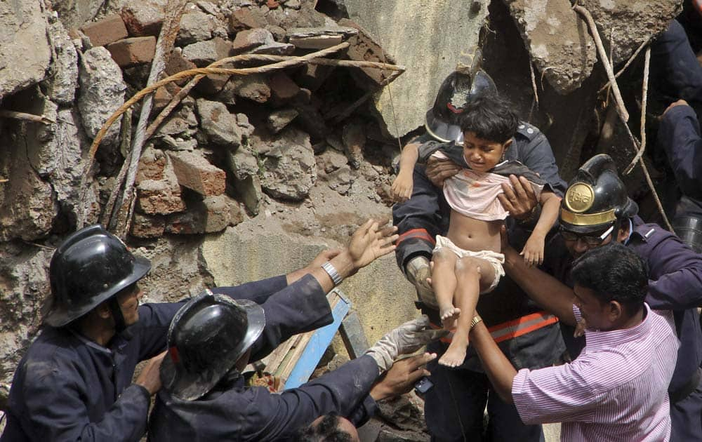 Fire officials rescue a girl from debris of a collapsed building in Mumbai.