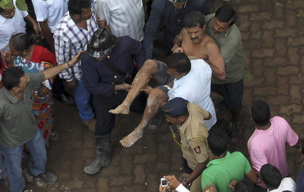 Rescue workers carry an injured man from the rubble of a building that collapsed in Mumbai.
