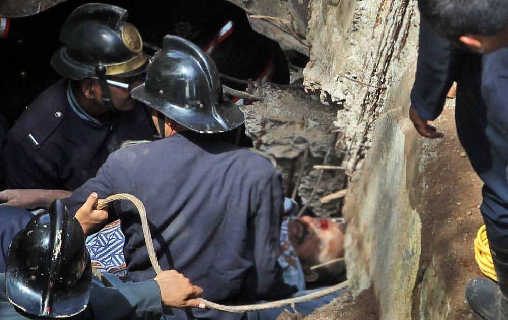 Fire officials rescues an injured person from debris of a collapse building in Mumbai.