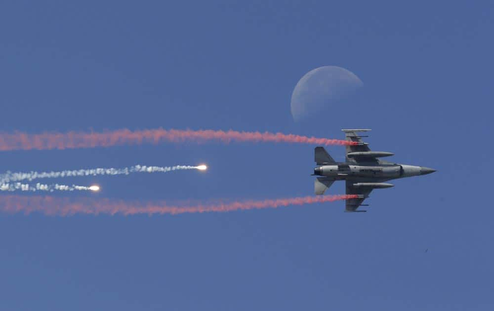 A South Korean Air Force F-16 fighter jet fires flare shells past the moon during the media day for the 65th anniversary of Armed Forces Day at Seoul military airport in Seongnam, South Korea.