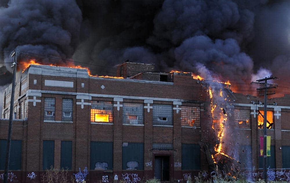 A part of the wall of an abandoned building in Detroit collapses in flames as Detroit firefighters try to contain the fire, in Detroit, Mich.