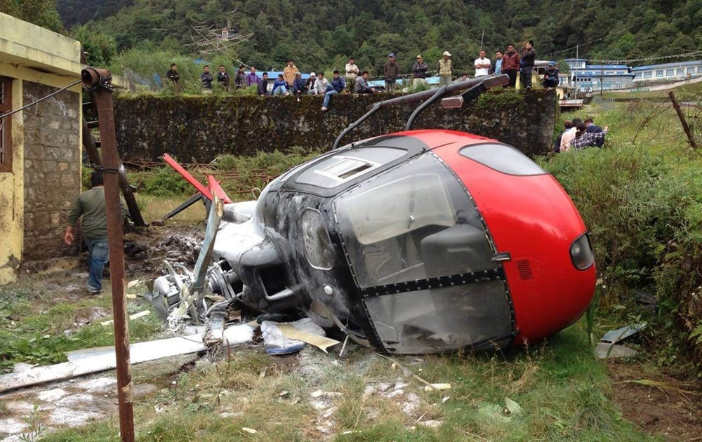 Nepalese look at a helicopter that crashed in Lukla, Nepal. The helicopter crashed while attempting to land near Mount Everest on Thursday, injuring all four people on board, Nepalese police said.