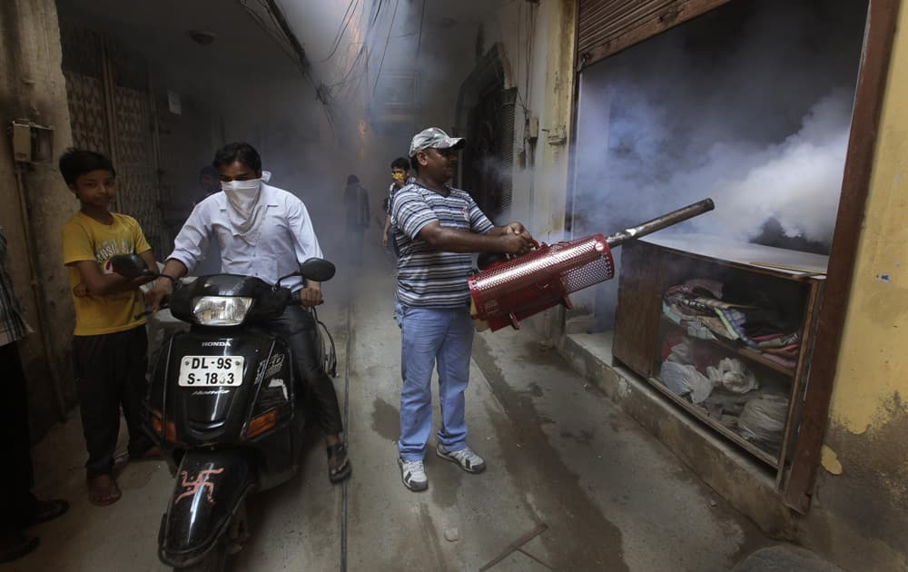 A man rides a motorbike past a Delhi municipal worker fumigating the area to prevent mosquitos from breeding in New Delhi.