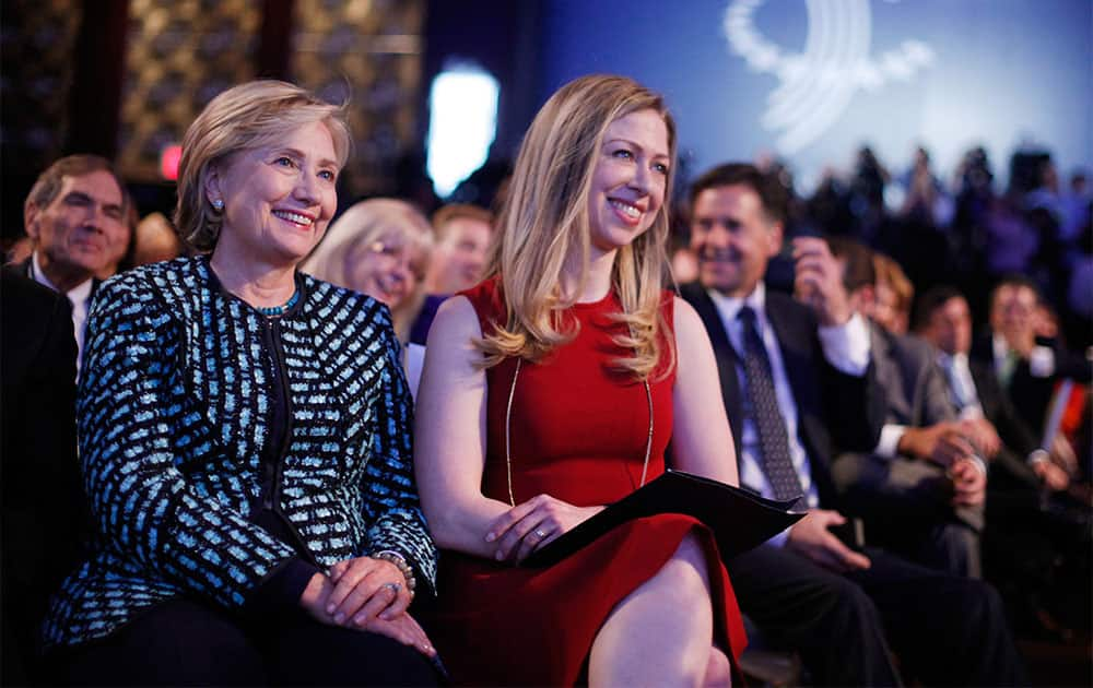 Former Secretary of State Hillary Rodham Clinton, left, and her daughter Chelsea Clinton, center, listen to President Barack Obama and former President Bill Clinton speak at the Clinton Global Initiative in New York.