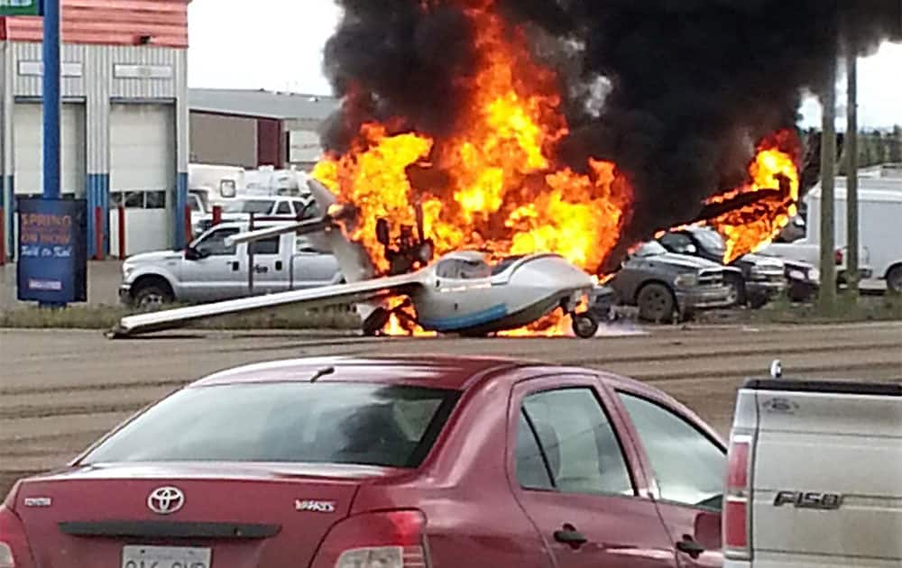 A plane is engulfed in flames in the middle of an intersection in Fort Nelson, British Columbia. Police in British Columbia say a pilot suffered only minor injuries.