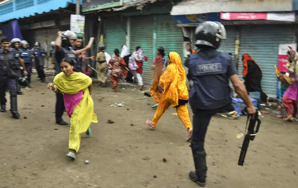 Bangladeshi garment workers run as police disperse them during a protest march in Narayanganj, near Dhaka, Bangladesh.