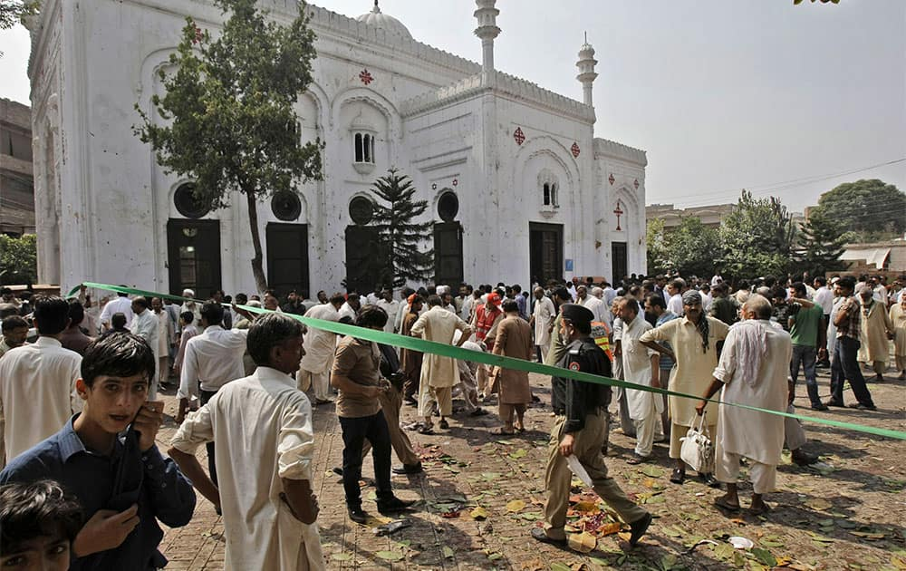 Police officers and civilians, gather at the site of a suicide attack on a church, in Peshawar, Pakistan.