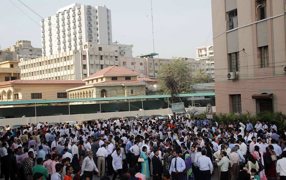 People rush out their apartments and offices after they felt a major earthquake that struck Baluchistan province in southwest Pakistan.