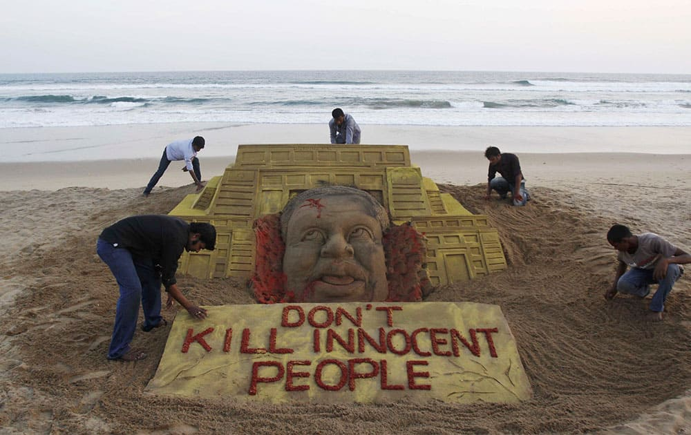 Indian sand artist Sudarshan Pattnaik, foreground left and his team pay tributes to the victims of the terror attack on a Kenya mall by creating a sand sculpture on the Bay of Bengal coast in Puri, Orissa state, India.