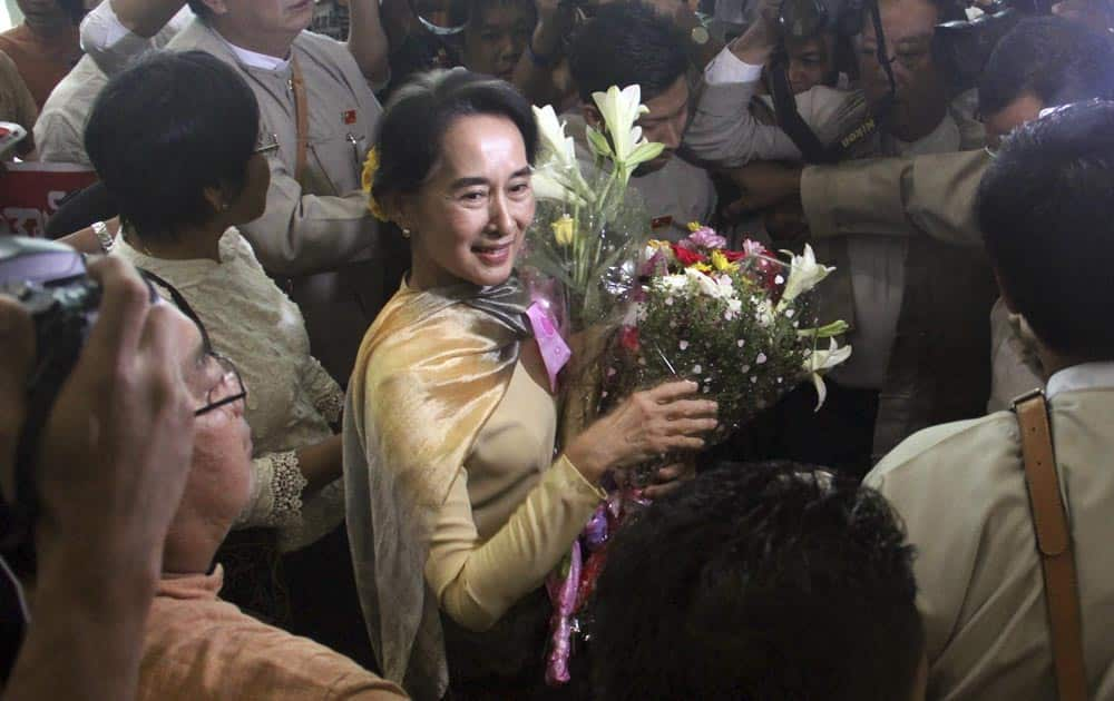 Myanmar Opposition leader Aung San Suu Kyi, is surrounded by her party supporters upon her arrival back from Singapore, at Yangon International airport in Yangon, Myanmar.