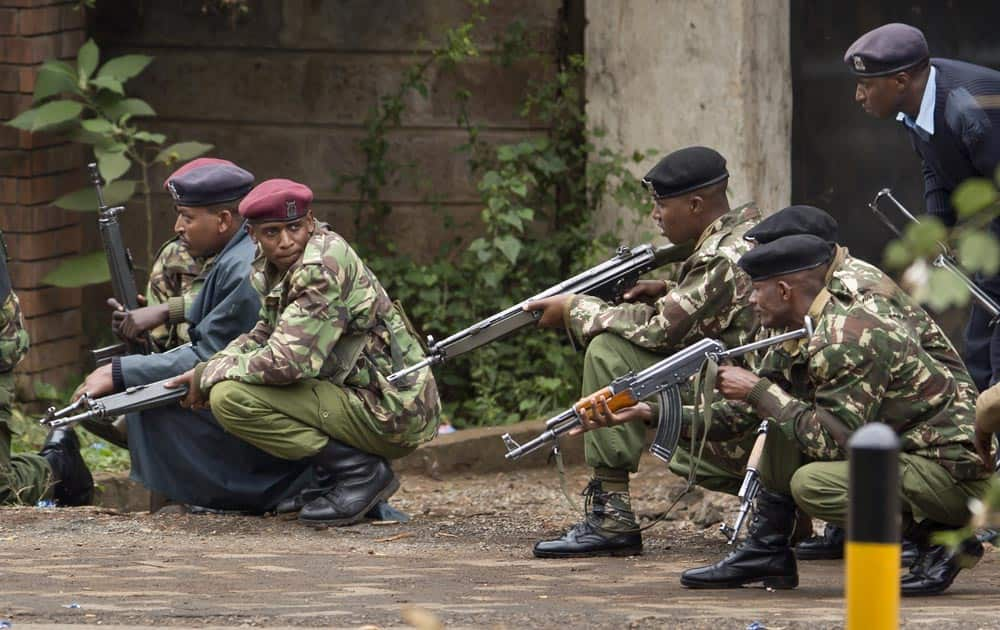 Armed police from the General Service Unit take cover behind a wall during a bout of gunfire, outside the Westgate Mall in Nairobi, Kenya.