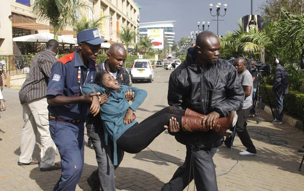 Security officer helps a wounded woman outside the Westgate Mall after gunmen opened fire and threw grenades.