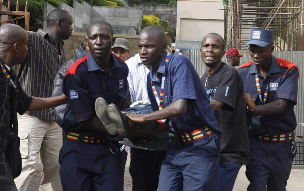 Security helps a wounded woman outside the Westgate Mall in Nairobi, Kenya.