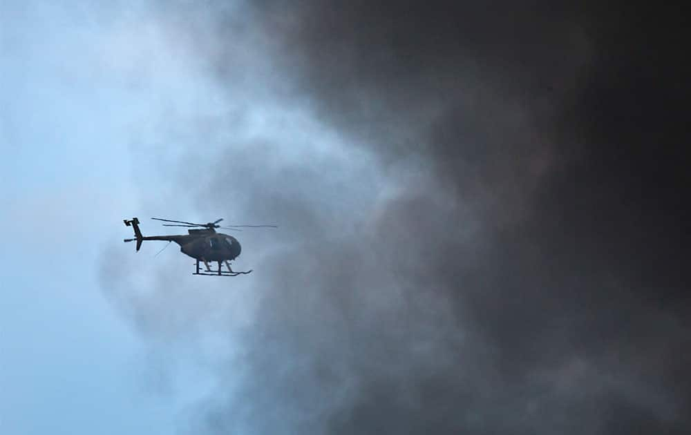 A Kenya Army helicopter flies behind a plume of black smoke billowing from the Westgate Mall, following large explosions and heavy gunfire, in Nairobi.