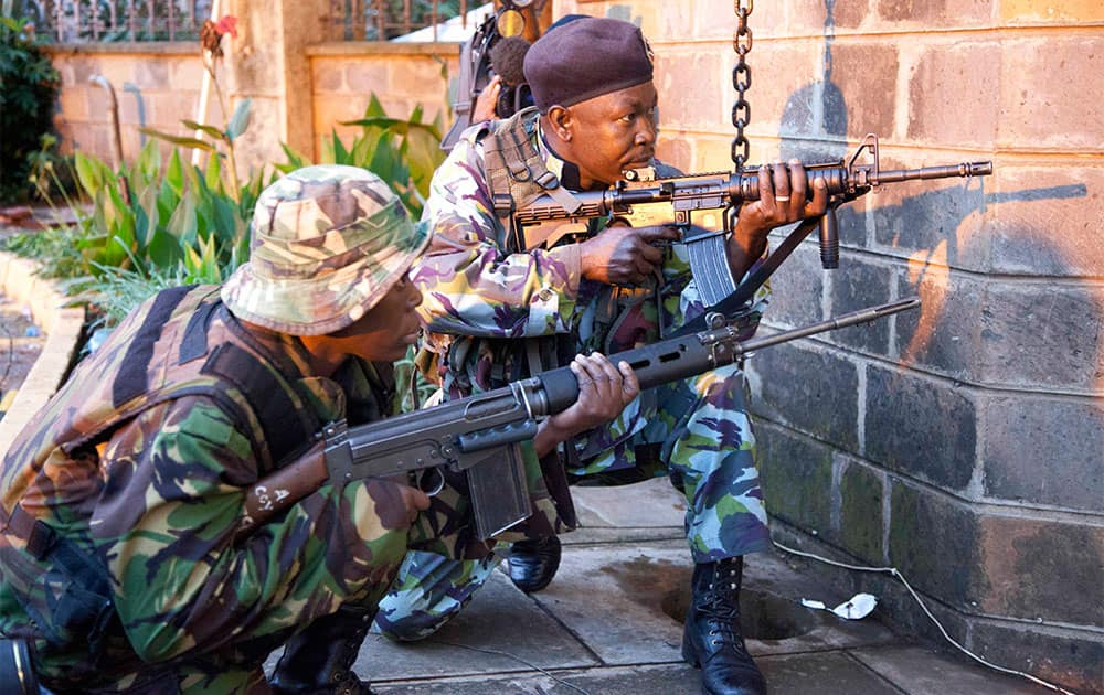 Kenya security personnel take cover outside the Westgate Mall after shooting started inside the mall early Monday morning.