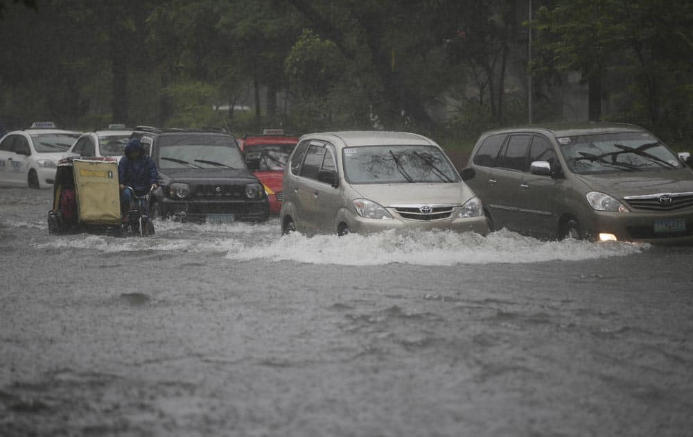 Vehicles cross a flooded street in Manila, Philippines.