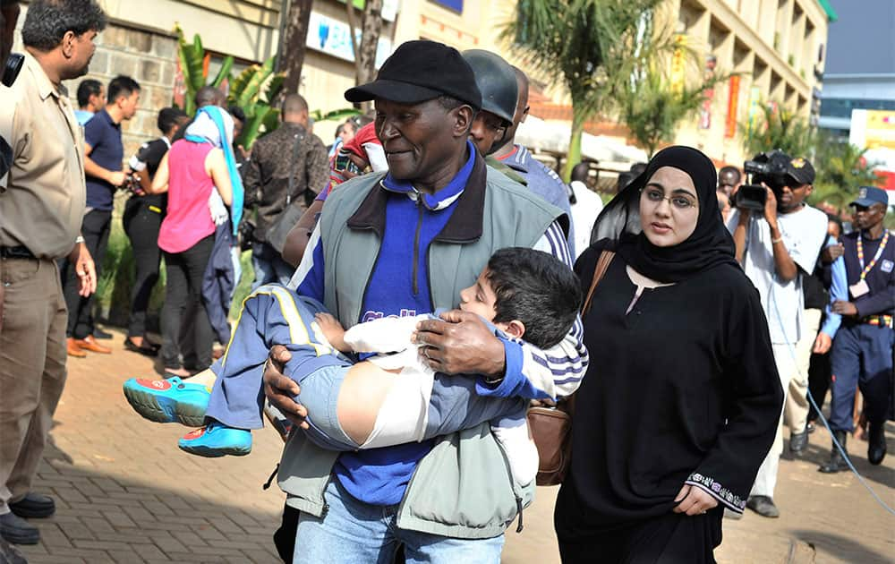 A rescue worker helps a child outside the Westgate Mall in Nairobi, Kenya, after gunmen threw grenades and opened fire during an attack that left multiple dead and dozens wounded.