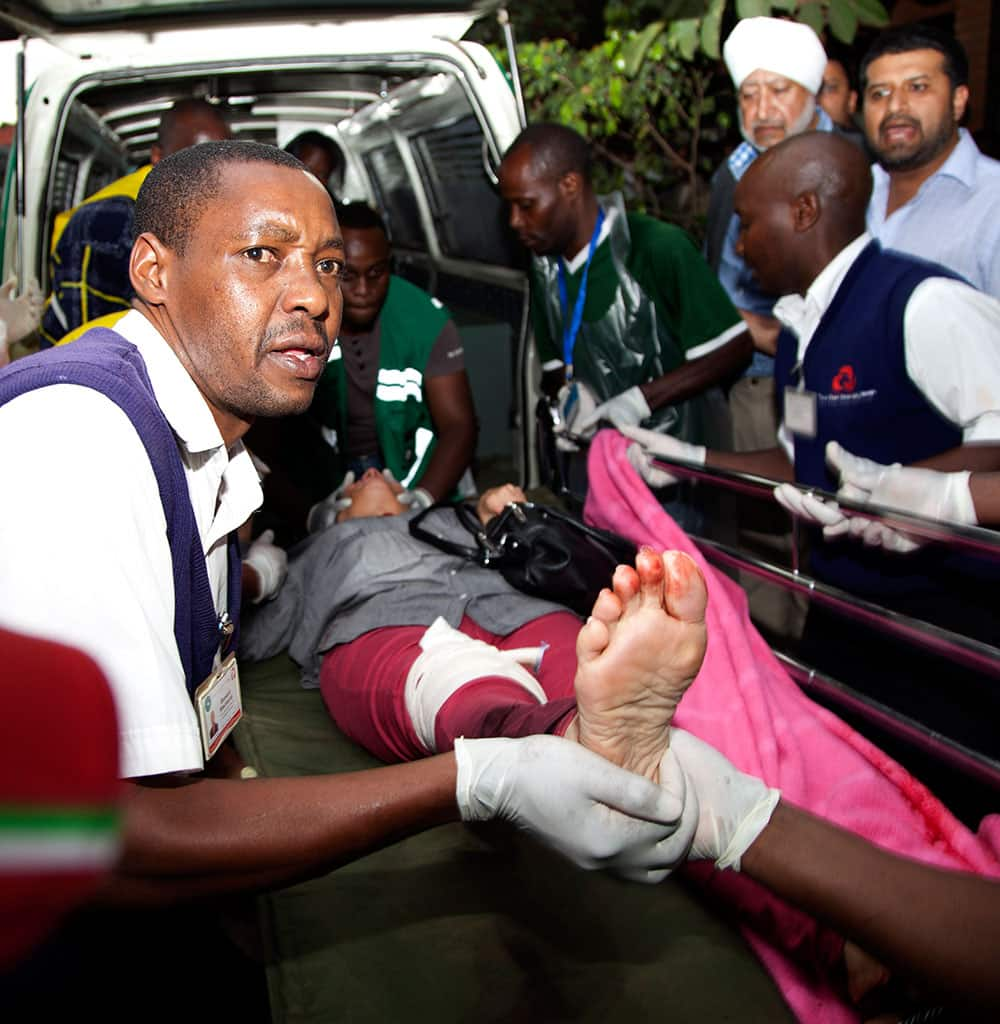 An injured person is helped on his arrival at the Aga Khan Hospital in Nairobi after an attack at the Westgate Mall, an upscale shopping mall in Nairobi, Kenya.