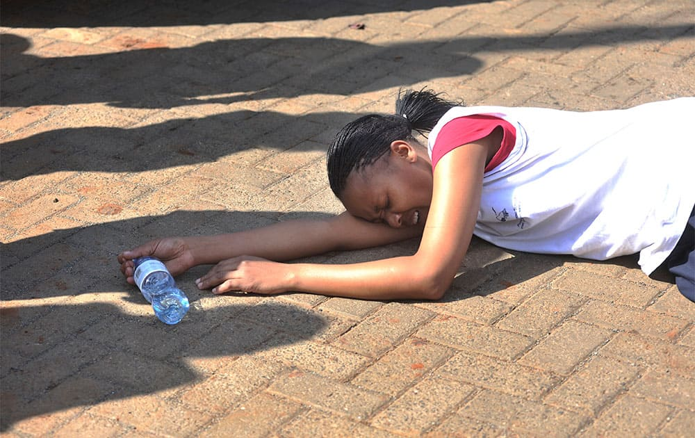 A rescued hostage collapses on the ground after being freed by police at Westgate Mall in Nairobi, Kenya.