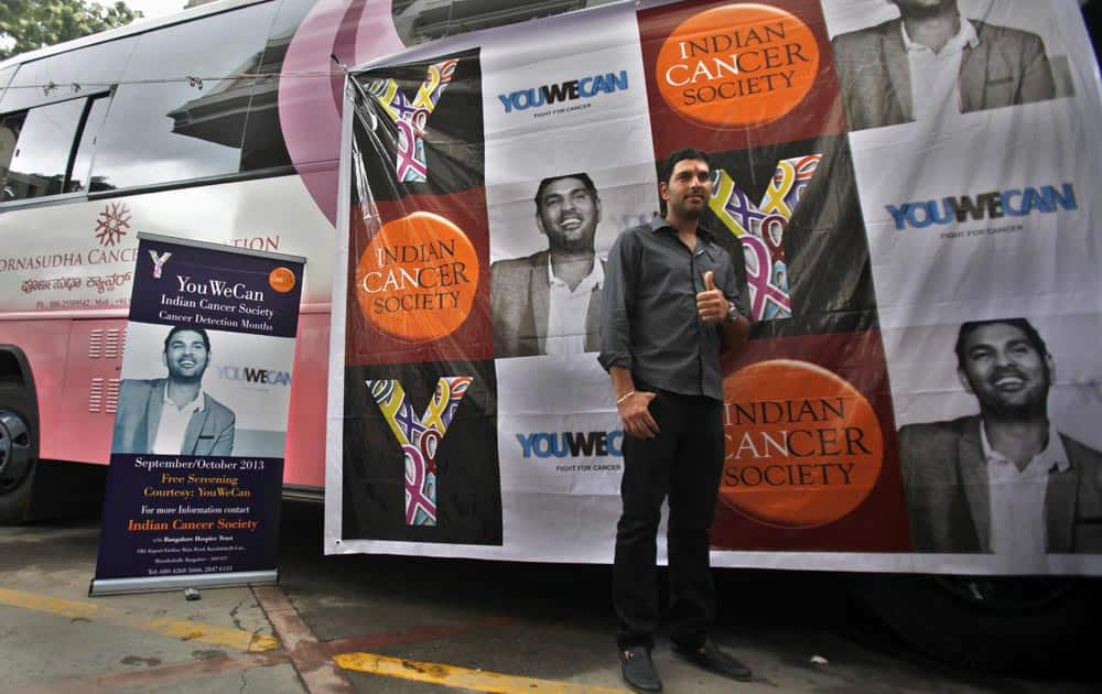 Yuvraj Singh gives a thumbs-up as he poses next to a vehicle fitted with cancer screening equipment in Bangalore.