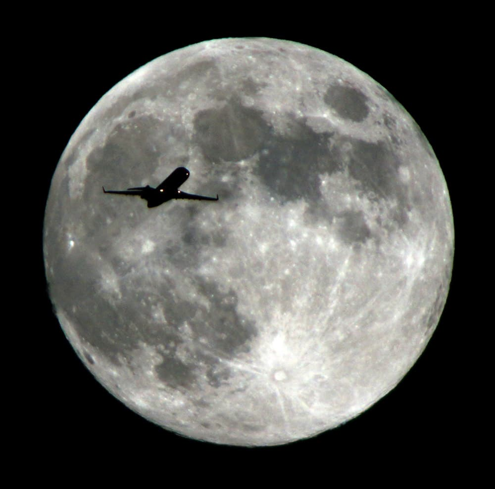 An airlines jet plane approaching Los Angeles International Airport crosses the moon as seen from Monterey Park Calif.