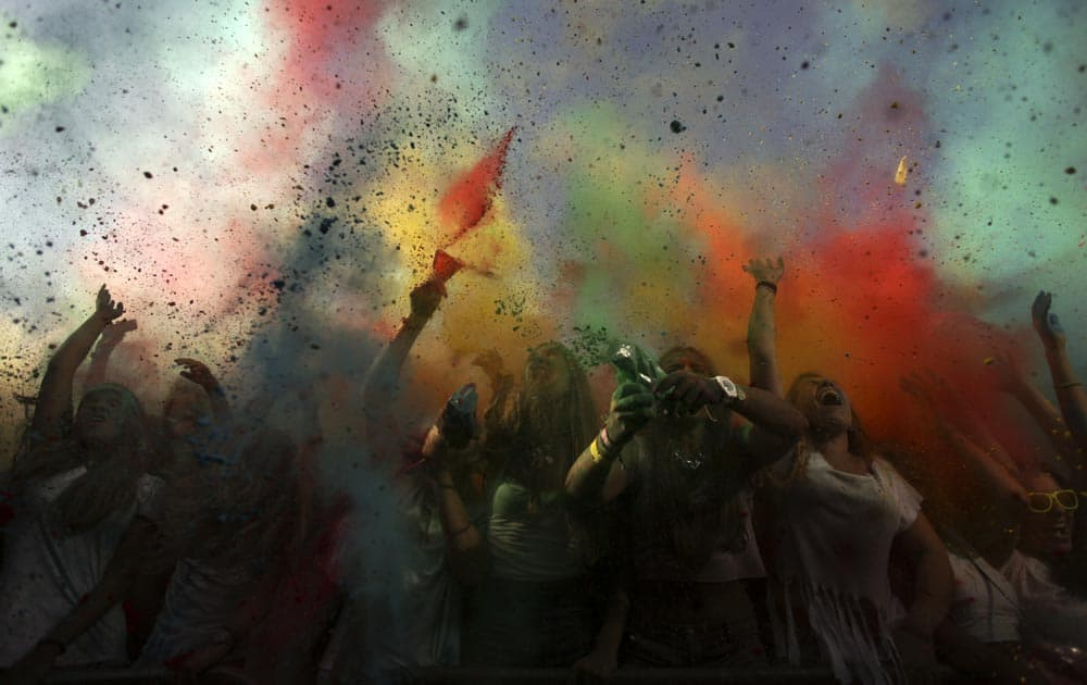 Revelers throw colored powders in the air during the Holi Festival of Colors in Lisbon.