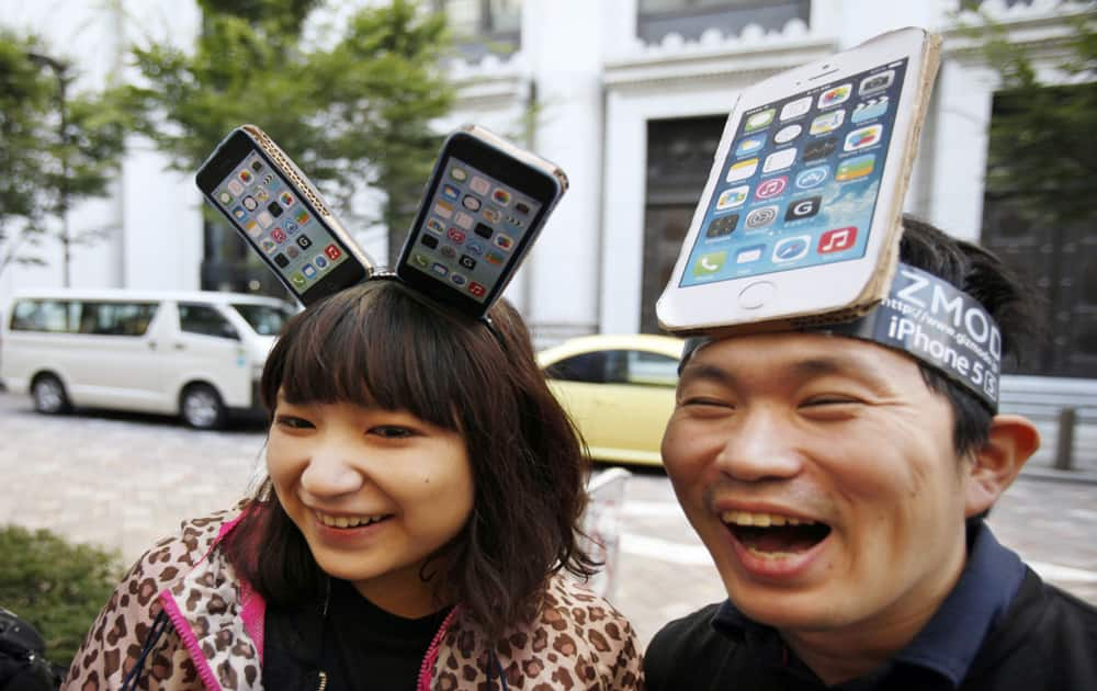 Yui Kashima, left, and Nobuhiko Matsuda wait to purchase an Apple`s new iPhone outside a store in Tokyo.