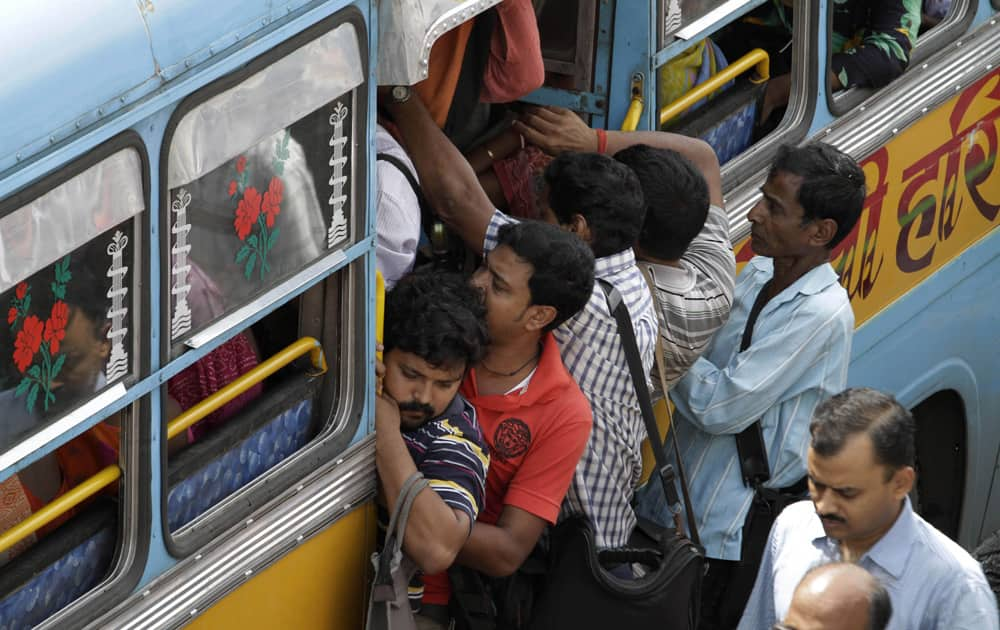 Commuters hang on the door of a crowded bus during a two-day strike called by private bus transport operators in Kolkata.